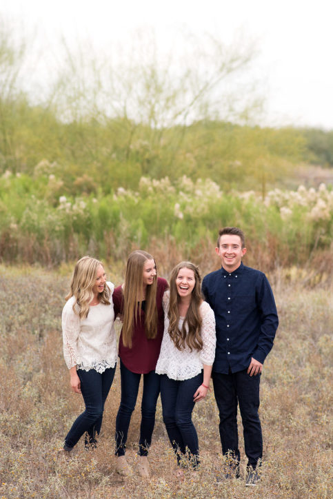 Siblings laughing photographed by Jubilee Family Photography in Gilbert, AZ.