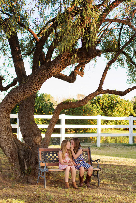 Sisters telling secrets under a tree.