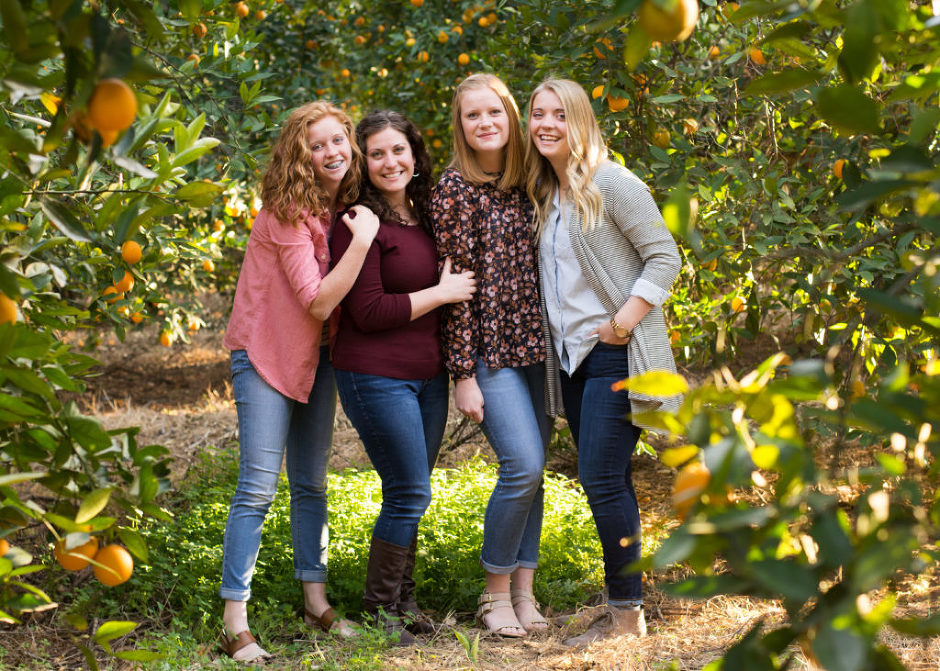 Sisters in orange grove photographed by Jubilee Family Photography in Gilbert, AZ.